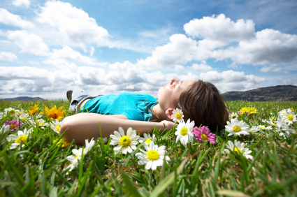 Woman lying in a field of flowers looking up at the sky